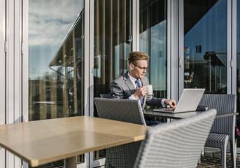 Finland, Helsinki, Businessman on cafe terrace