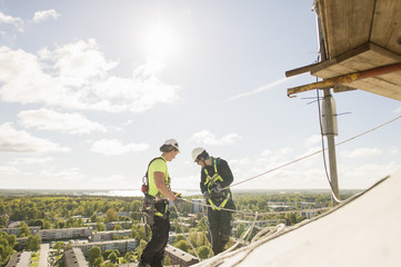Sweden, Narke, Orebro, Construction workers on roof