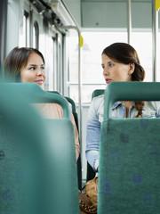 Finland, Helsinki, Two young women in bus seen from behind seatbacks