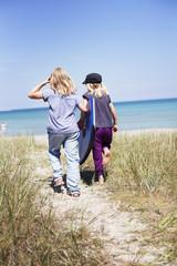 Sweden, Gotland, Faro, Two girls (8-9, 10-11) walking on beach