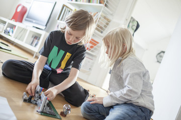 Sweden, Vastergotland, Lerum, Siblings (6-7, 8-9) playing with plastic blocks