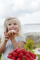 Sweden, Uppland, Roslagen, Girl (6-7) eating strawberry dessert outdoors