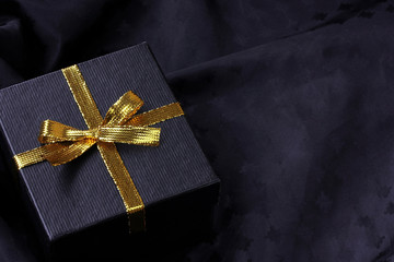 black gift box with golden ribbon