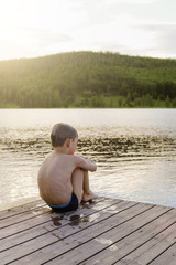 Rear view of shirtless boy sitting on pier by the lake