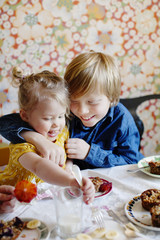 Sweden, Boy (10-11) and girl (2-3) eating cake