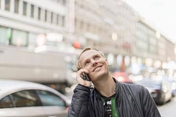 Sweden, Uppland, Stockholm, Kungsgatan, Mid-adult man talking on phone