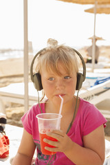 Turkey, Alanya, Portrait of blonde girl (4-5) wearing headphones and drinking with straw on beach