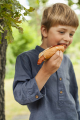 Sweden, Uppland, Runmaro, Barrskar, Portrait of boy (4-5) eating hot dog