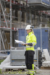 Construction worker looking at blueprints while standing at construction site