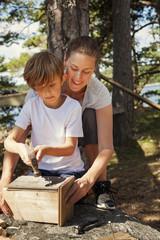 Sweden, Uppland, Runmaro, Barrskar, Mother helping son (6-7) to build birdhouse
