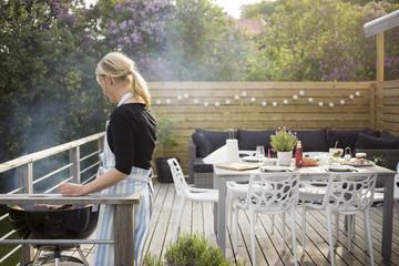 Sweden, Vastergotland, Lerum, Mature woman cooking on patio