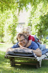 Sweden, Skane, Mossby, Portrait of daughter with father lying on deckchair