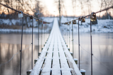 Locks on a rope bridge over frozen water