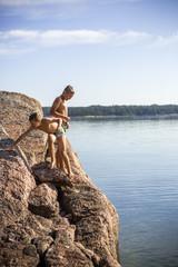 Finland, Uusimaa, Baltic Sea, Porvoo, Boys (8-9, 10-11) in swimwear on rock above sea