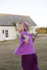 Sweden, Gotland, Faro, Girl (8-9) running in backyard