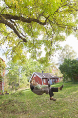 Sweden, Sodermanland, Jarna, Grandmother with baby boy (12-17 months) on swing