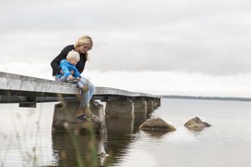Sweden, Gotland, Farosund, Mother sitting with son (12-17 months) on jetty