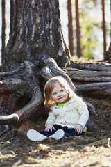 Finland, Keski-Suomi, Jyvaskyla, Little girl (2-3) sitting next to tree in forest