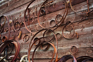 Ancient medieval rusty metal hardware and forged rim on a wooden wall.