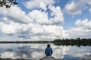 Rear view of woman sitting on rock by lake against cloudy sky