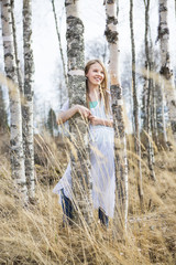 Finland, Keski-Suomi, Aanekoski, Smiling girl (12-13) standing by birch tree in forest