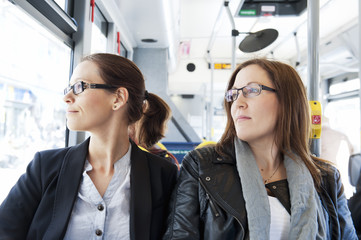 Two beautiful female friends traveling by bus