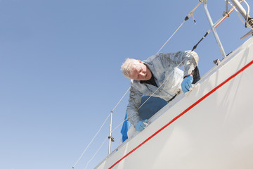 Senior man cleaning sailboat
