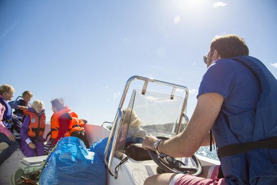 Sweden, Swedish West Coast, Halland, Kungsbackafjorden, Man with kids (6-7, 8-9, 10-11) on motor boat