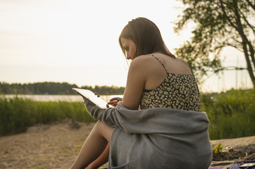 Young woman using digital tablet while sitting outdoors