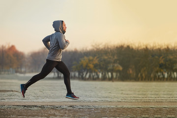 Photo sur cadre textile Glisse hiver Young athletic man running at park during cold autumn morning