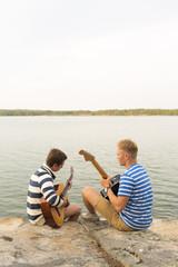 Young men playing guitar while sitting near seaside