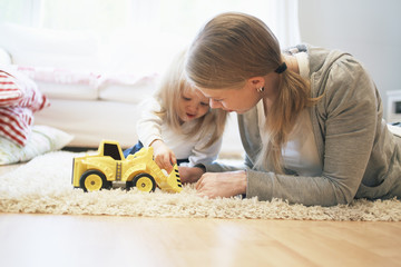 Mother playing with child (2-3) on carpet