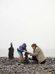 Sweden, Oland, Mother and daughter (4-5) building cairn on beach
