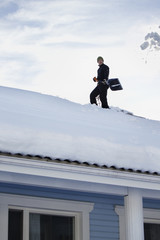 Finland, Mellersta Finland, Jyvaskyla, Man removing snow from house roof with snow shovel