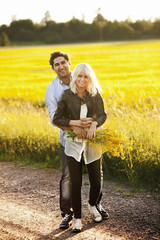 Sweden, Ostergotland, Smiling young couple embracing by field