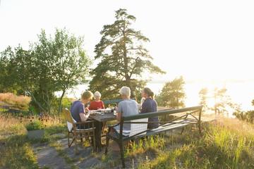 Sweden, Sodermanland, Stockholm Archipelago, Haninge, Dalaro, Family (12-13) having dinner in garden