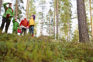 Finland, Keski-Suomi, Jyvaskyla, Father with daughters (2-5, 6-8) standing in forest and shielding from sun