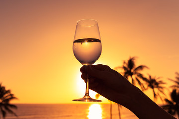 Person holding glass of wine on the beach against a beautiful sunset.