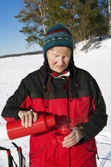 Sweden, Gastrikland, Ockelbo, Woman pouring coffee from thermos outdoors