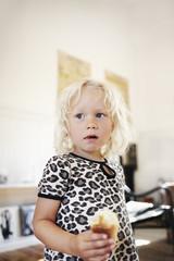 Sweden, Portrait of blond girl (4-5) eating sweet bun