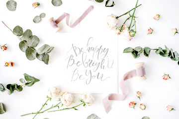 inspirational quote be happy, be bright, be you written in calligraphy style on paper with pink roses and eucalyptus branches on white background. flat lay, top view
