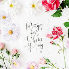 "inspirational quote ""follow your soul it knows the way"" written in calligraphy style on paper with pink, red roses, chamomiles and leaves isolated on white background. Flat lay, top view"