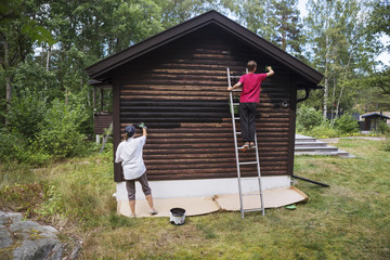 Sweden, Stockholm Archipelago, Sodermanland, Orno, Teenage boy (14-15) painting log cabin with his mother