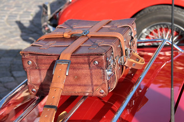 leather suitcase on a classic car