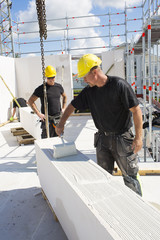 Sweden, Ostergotland, Linkoping, Construction workers preparing building blocks to build wall