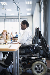 Finland, Helsinki, Man in wheelchair working in office