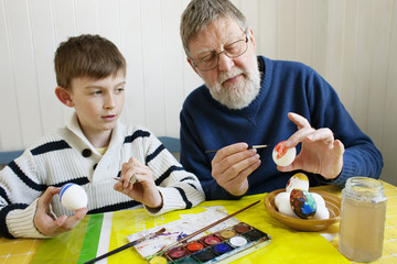 Grandfather with grandson (8-9) decorating Easter eggs