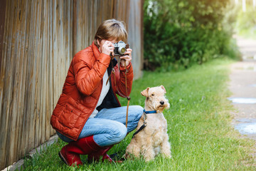 Girl with retro photo camera and lakeland terrier dog near the wooden fence outdoors