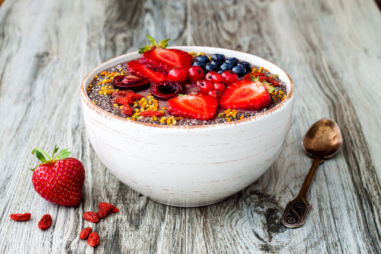Acai breakfast superfoods smoothies bowl with chia seeds, bee pollen, goji berry toppings and peanut butter. Overhead, top view.