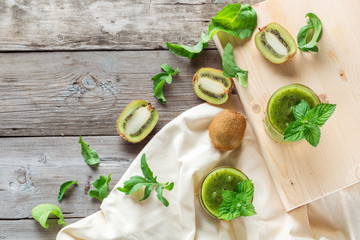 Ingredients for preparation of: kiwi, arugula, mint and two glasses smoothies